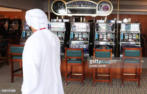 A man walks past disused slot machines in the gaming arcade of The Queen Elizabeth II luxury cruise liner also known as the QE2 docked at Port Rashid...