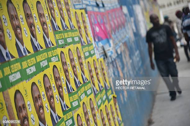 TOPSHOT A man walks past election posters of Presidential candidate Jude Celestin from the Lapeh Political Party in PortauPrince on September 19 2016...