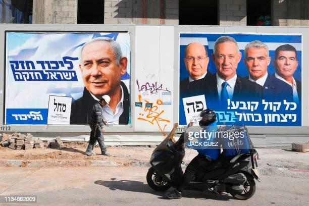 A man walks past electoral campaign posters bearing the portraits of Israel's Prime Minister Benjamin Netanyahu leader of the Likud party and retired...