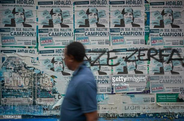 A man walks past electoral posters against Paris Mayor Socialist Anne Hidalgo who is fighting for a second term as Parisians go to the polls today in...