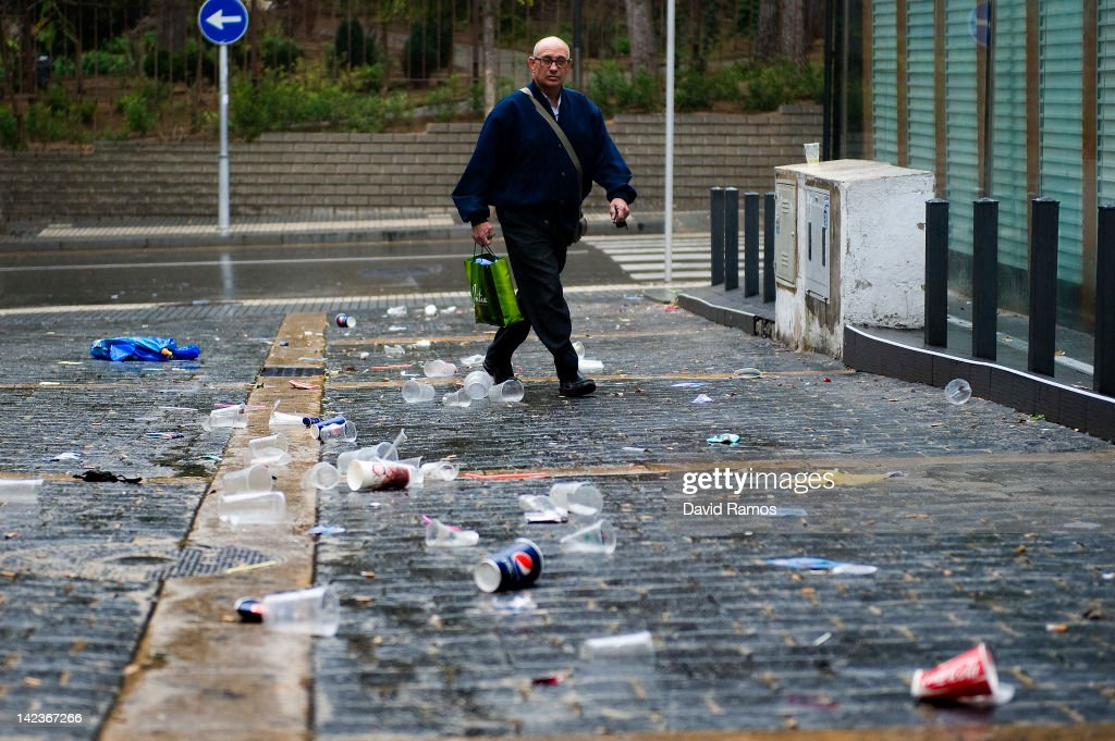 A man walks past empty beer cans, plastic glasses and rubbish left by students after the second night of parties during the SalouFest on April 3, 2012 in Salou, Spain. Saloufest is a university sports tour attended by thousands of British students taking part in a variety of competitions and parties over the Easter period in the Catalan village of Salou.