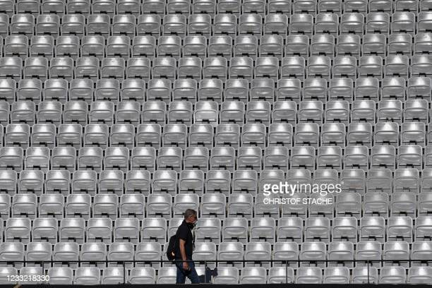 Man walks past empty stands during a training session of Denmark's national football team on June 1, 2021 in Innsbruck, Austria, on the eve of a...