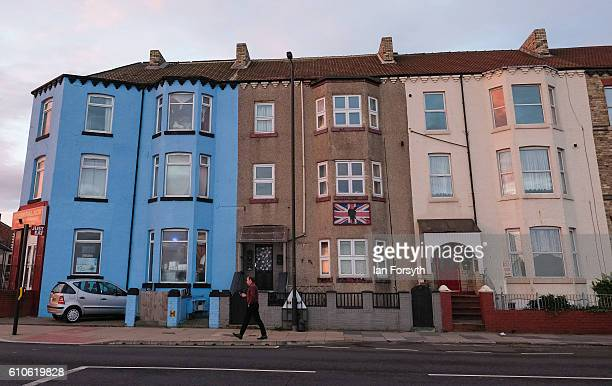 A man walks past flats on Redcar seafront on September 27 2016 in Redcar United Kingdom One year on since the SSI steel making plant at Redcar was...