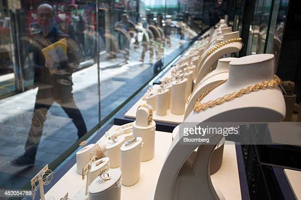 A man walks past gold jewelry displayed in the window of a Chow Tai Fook Jewellery Group Ltd store in the shopping district of Tsim Sha Tsui in Hong...