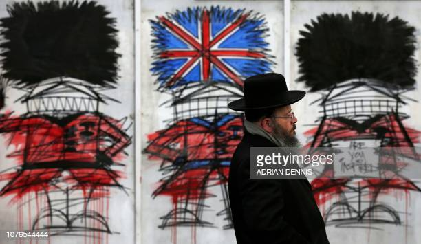 A man walks past graffiti depicting British soldiers from the Queen's Guard regiments one with a Union Flagthemed Bearskin hat in central London on...