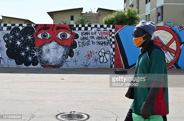 Man walks past graffiti on a wall depicting hygiene measures to curb the spread of the COVID-19 coronavirus in Abidjan on May 15, 2020. - Ivory Coast...