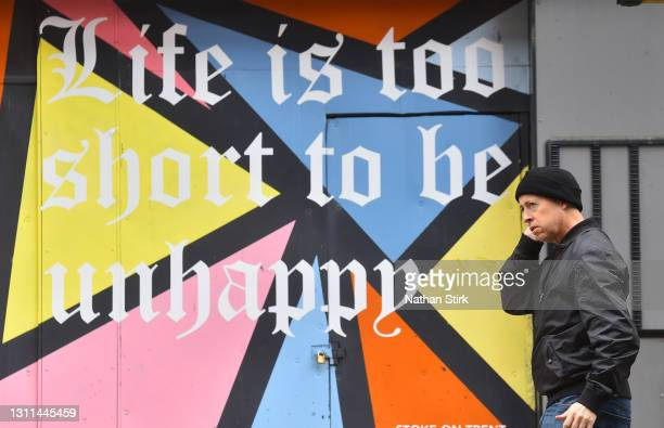 Man walks past graffiti saying 'life is too short to be unhappy' whilst shopping in Hanley on April 08, 2021 in Stoke-on-Trent, England .
