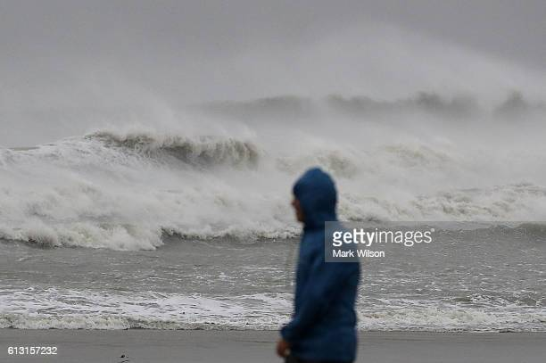A man walks past heavy surf caused by Hurricane Matthew October 7 2016 on Cocoa Beach Florida Hurricane Matthew passed by offshore as a catagory 3...