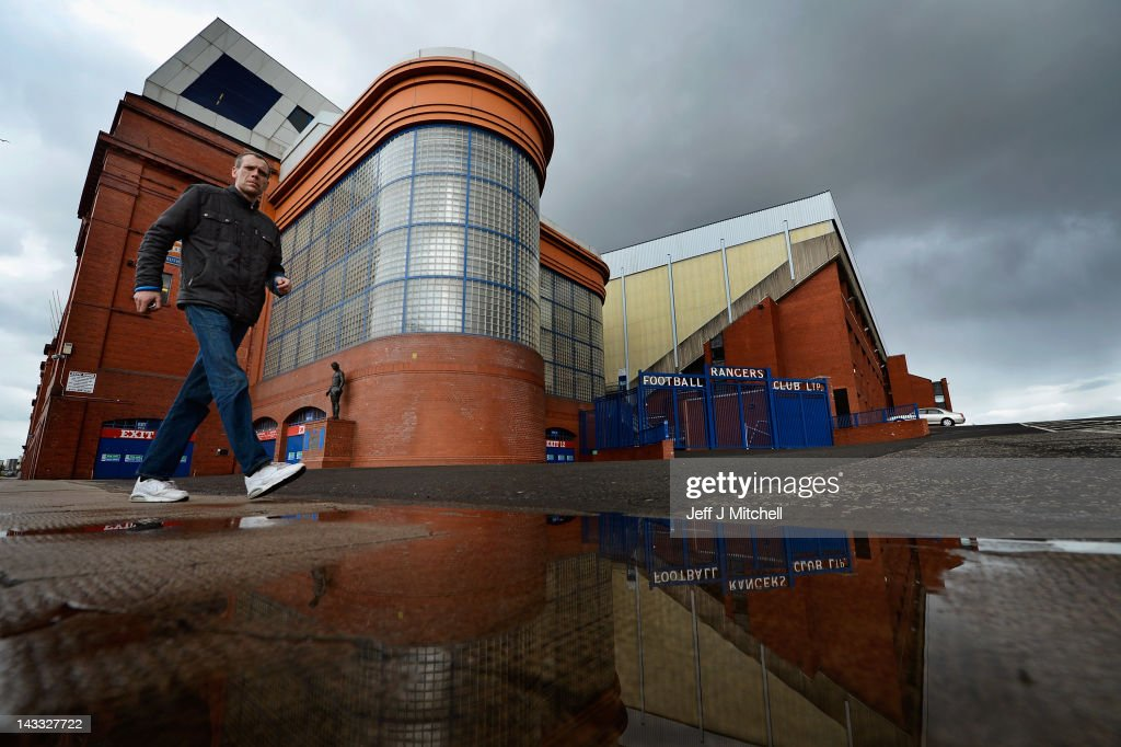 A man walks past Ibrox Stadium, home to Glasgow Rangers Football Club on April 24, 2012 in Glasgow, Scotland. Rangers have received a 12 month transfer embargo and a GBP 160,000 fine from the Scottish FA, while current owner Craig Whyte as been banned for life from any involvement in Scottish Football.