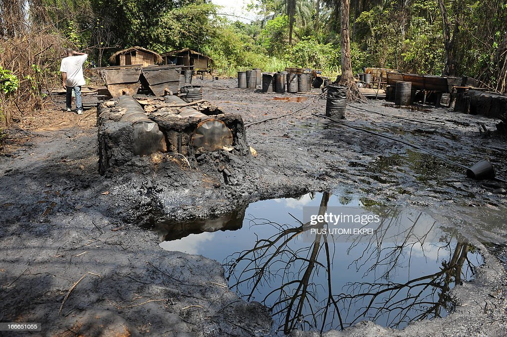 A man walks past illegal oil distillery camps operated by oil thieves in Bayelsa State of the Niger Delta April 11, 2013. Shell Development Company of Nigeria (SPDC) had threatened to shut down production in April for nine days in the entire Nembe Trunk Line to remove a number of bunkering points on pipelines vandalised by oil thieves in the region. Since 2009, SPDC has experienced an upsurge in vandalisation of pipeline network by criminals causing severe environmental devastation and forcing the company to lose 60,000 barrels daily this year. AFPPHOTO