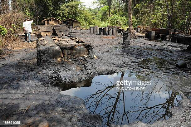 A man walks past illegal oil distillery camps operated by oil thieves in Bayelsa State of the Niger Delta April 11 2013 Shell Development Company of...