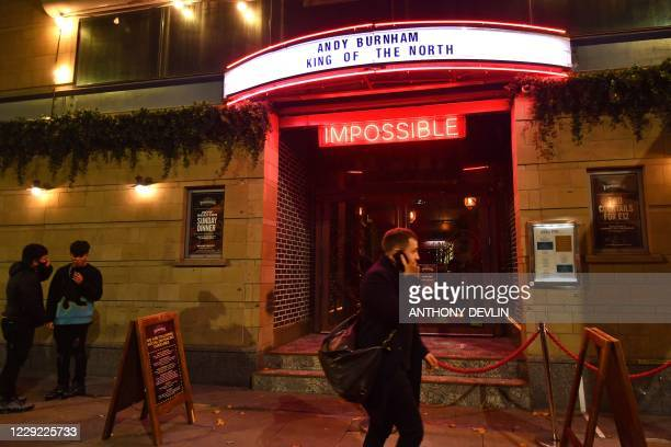 A man walks past Impossible Bar on Peter Street in Manchester city centre northwest England ahead of new coronavirus restrictions coming into force...