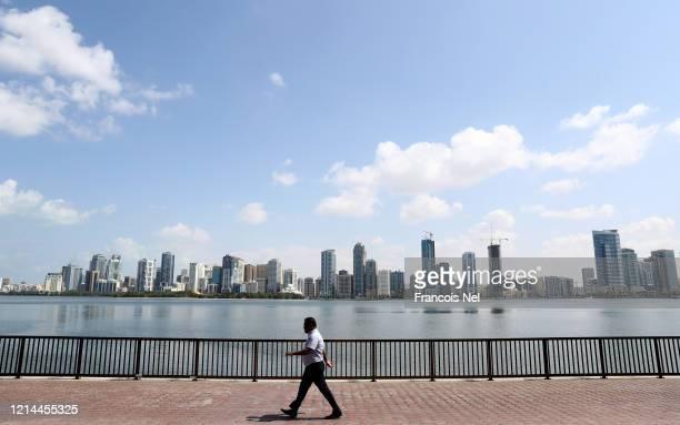 A man walks past Khalid Lake on March 24 2020 in Sharjah United Arab EmiratesOn March 11 the World Health Organization declared coronavirus a global...