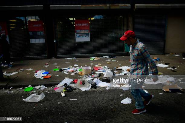 A man walks past looting damage during widespread unrest following the death of George Floyd on May 31 2020 in Philadelphia Pennsylvania Protests...