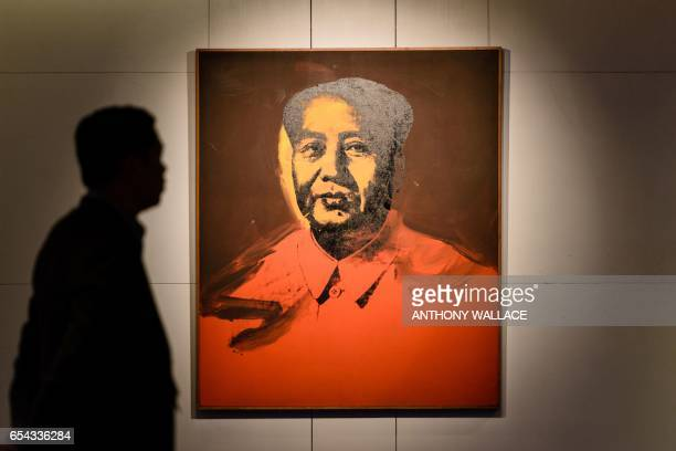 A man walks past Mao by US artist Andy Warhol an acrylic and silkscreen ink on canvas during a preauction preview by Sotheby's in Hong Kong on March...