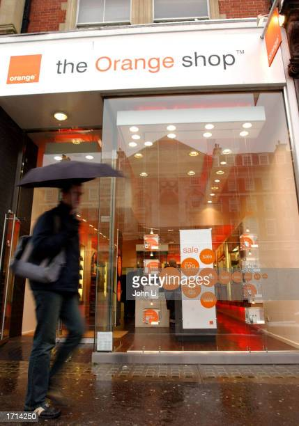 A man walks past mobile phone retailer and operator The Orange Shop January 8 2003 in London Big name retailers have reported slow sales before...