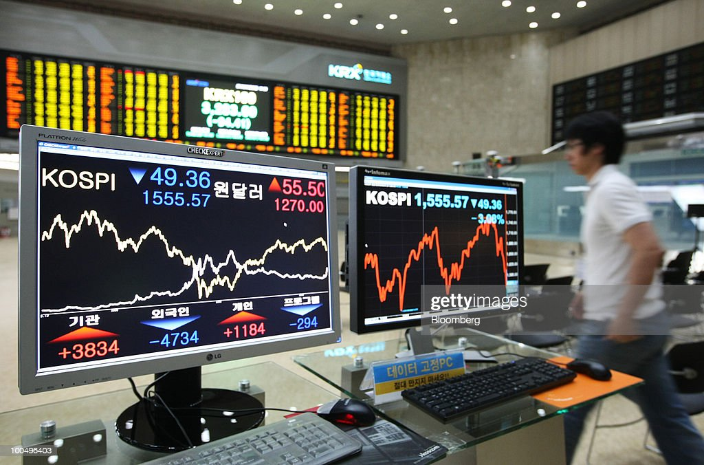 A man walks past monitors displaying the Korea Composite Stock Price Index (KOSPI) and the exchange rate between the U.S. dollar and the South Korean won at the Korea Stock Exchange in Seoul, South Korea, on Tuesday, May 25, 2010. Asian stocks and the won plunged to 10-month lows after a report that North Korean leader Kim Jong Il ordered his military to prepare for combat last week. Photographer: SeongJoon Cho/Bloomberg via Getty Images