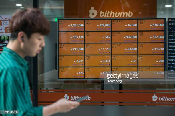 A man walks past monitors displaying the prices of cryptocurrencies at a Bithumb exchange office in Seoul South Korea on Wednesday June 20 2018...