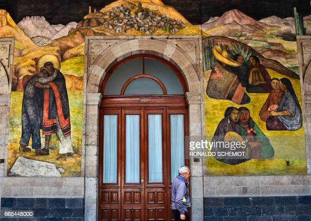 A man walks past murals by Mexican artist Diego Rivera in the Education Secretariat in Mexico City on April 2017 Rivera was the most visible figure...