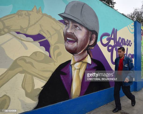 A man walks past murals on the walls of a municipal stadium in Lima on July 17 depicting national sportsmen and women participating in the Lima2019...