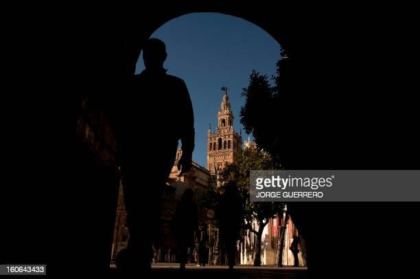 A man walks past next to the Giralda of Sevilla on February 4 2013 AFP PHOTO/ JORGE GUERRERO