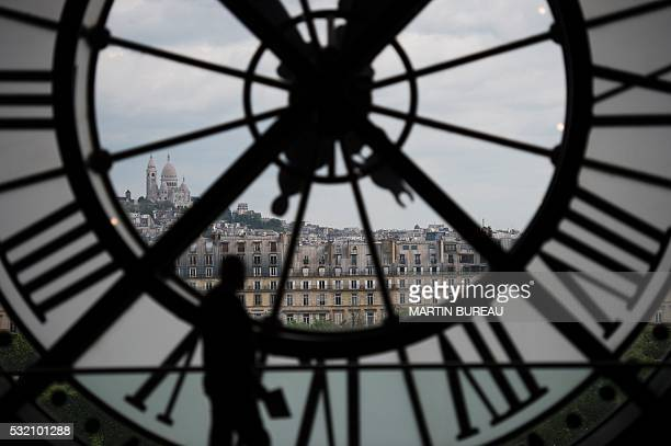 A man walks past one of the clocks of the Orsay museum on May 18 2016 in Paris / AFP / MARTIN BUREAU