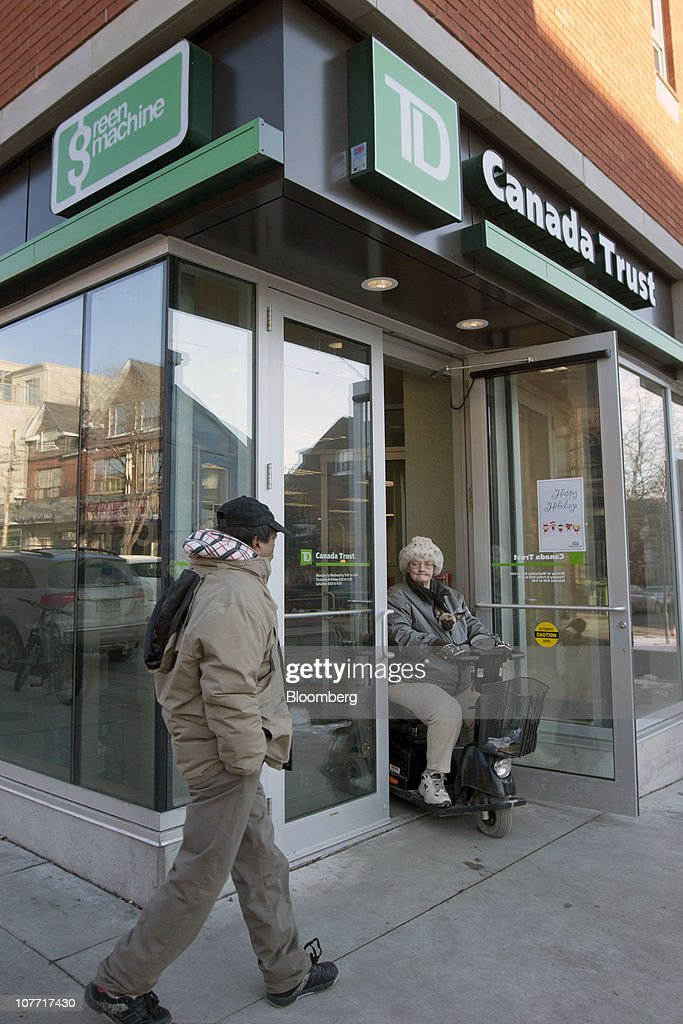 A man walks past one of Toronto-Dominion Bank's (TD) Canada Trust branches in Toronto, Ontario, Canada, on Tuesday, Dec. 21, 2010. Toronto-Dominion Bank agreed to buy Chrysler Financial Corp. from Cerberus Capital Management LP for $6.3 billion in cash, adding an auto-finance company in its second-largest acquisition. Photographer: Norm Betts/Bloomberg via Getty Images