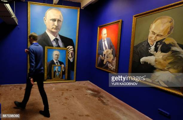A man walks past paintings depicting Russian president Vladimir Putin at the 'SUPERPUTIN' exhibition at UMAM museum in Moscow on December 6 2017 /...