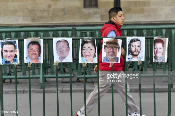 A man walks past pictures of members of the press during a protest against the murder or disappearance of more than 140 journalists and...
