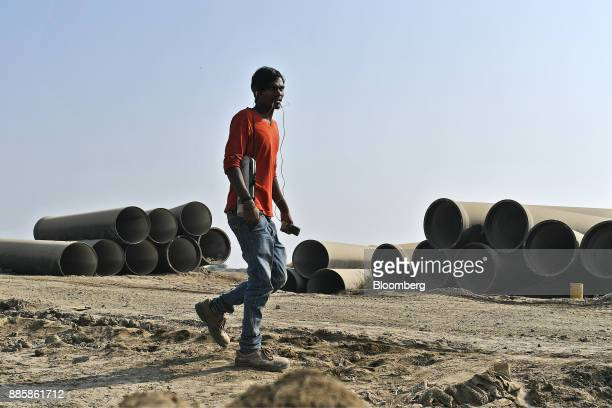 A man walks past pipes stacked at the project site for a 920squarekilometer industrial area located on the DelhiMumbai Industrial Corridor near the...