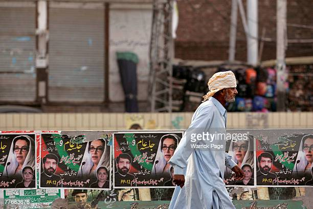 A man walks past political posters of Benazir Bhutto November 5 2007 in Rawalpindi Pakistan Pakistani President Pervez Musharraf declared a state of...