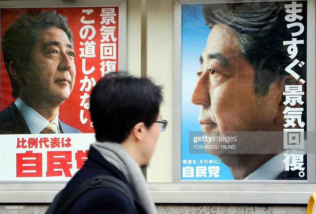 A man walks past posters of Japanese Prime Minister and ruling Liberal Democratic Party (LDP) leader Shinzo Abe displayed at the LDP headquarters in Tokyo on December 4, 2014. Abe's ruling party is set for a landslide win in the December 14 election, according to opinion polls. AFP PHOTO / Yoshikazu TSUNO