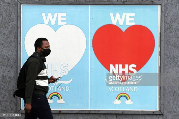 A man walks past posters paying tribute to NHS staff who continue to work to help patients during the coronavirus COVID19 outbreak in Glasgow on...
