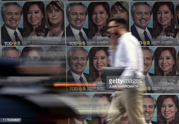 A man walks past propaganda of the Frente de Todos opposition party depicting presidential candidate Alberto Fernandez and his running mate former...