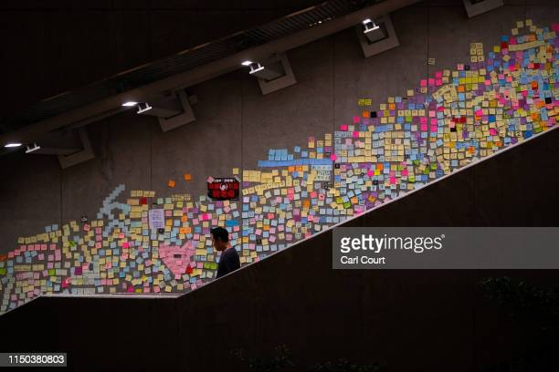 A man walks past protest messages written on postit notes on the wall of a stairway near the Legislative Council building on June 17 2019 in Hong...