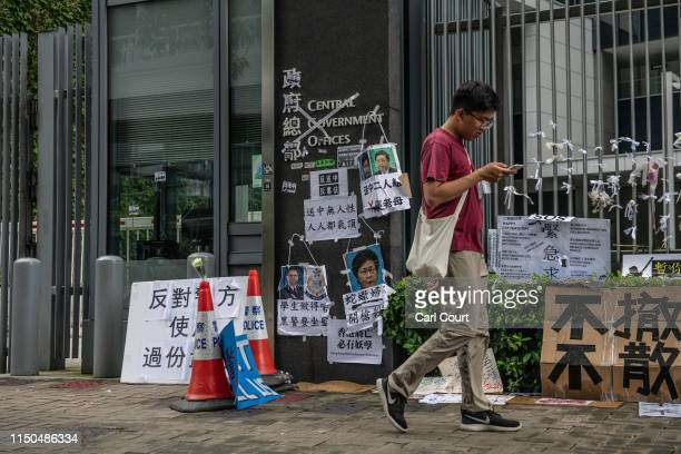 A man walks past protest posters on the entrance to the Legislative Council building on June 18 2019 in Hong Kong Hong Kongs Chief Executive Carrie...
