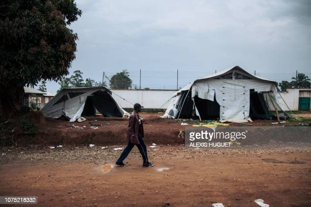 A man walks past ransacked tents by demonstrators near the Ebola transit centre in Beni following a demonstration against the postponement of...