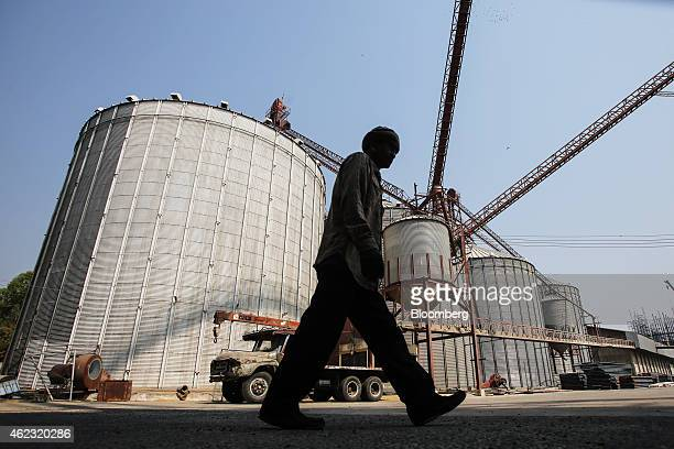 A man walks past rice storage silos prior to a preauction rice inspection at the warehouse of the Siri Chokchai rice mill in Chok Chai Nakhon...