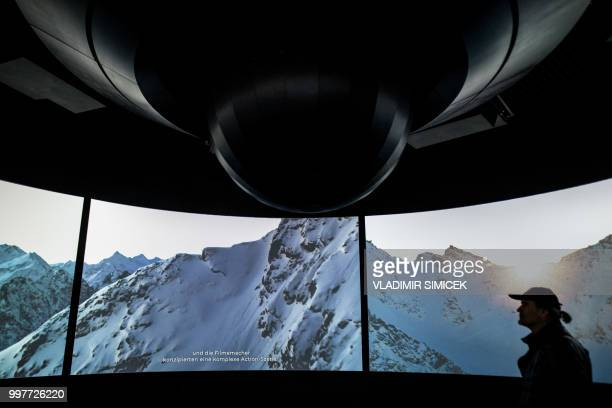 A man walks past screens during a visit at the James Bond cinematic installation named '007 ELEMENTS' on July 11 2018 at the top of the Gaislachkogl...