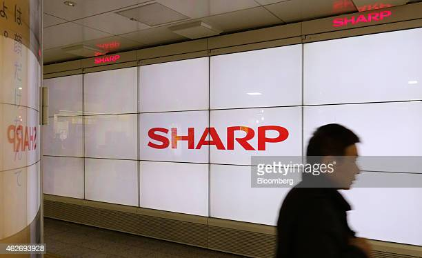 A man walks past Sharp Corp liquidcrystal displays showing the company's logo in Tokyo Japan on Tuesday Feb 3 2015 Sharp cut its forecast to an...