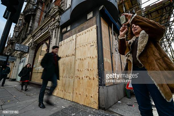 A man walks past sheets of wood covering a mural by British graffiti artist Banksy featuring the character Cosette from French author Victor Hugo's...