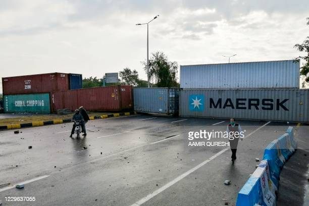 Man walks past shipping containers placed by the authorities to block the Islamabad-Rawalpindi highway to stop protesters from religious party...