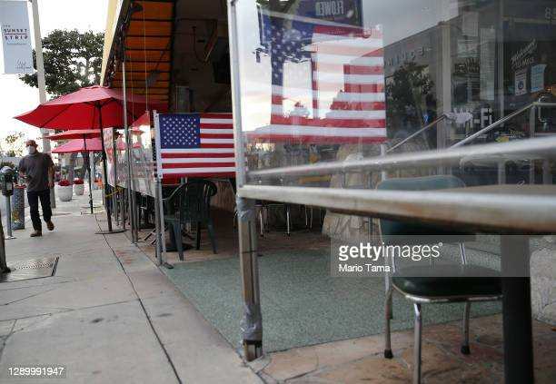 Man walks past shuttered outdoor restaurant seating decorated with American flags on the first day of new stay-at-home orders on December 7, 2020 in...