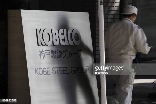 A man walks past signage for Kobe Steel Ltd displayed outside the company's offices in Tokyo Japan on Friday Oct 27 2017 Kobe Steel said yesterday it...