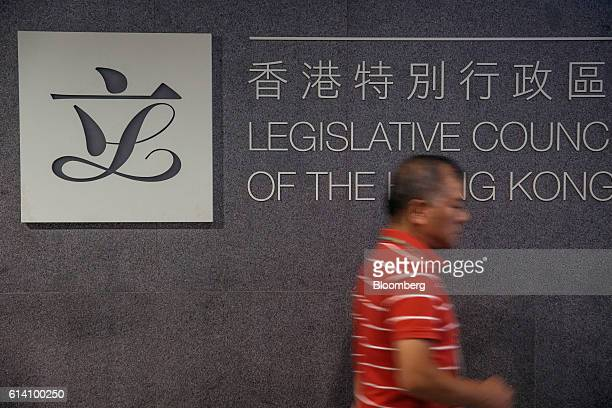 A man walks past signage for the Legislative Council ahead of an oathtaking ceremony at Hong Kong's Legislative Council in Hong Kong China on...