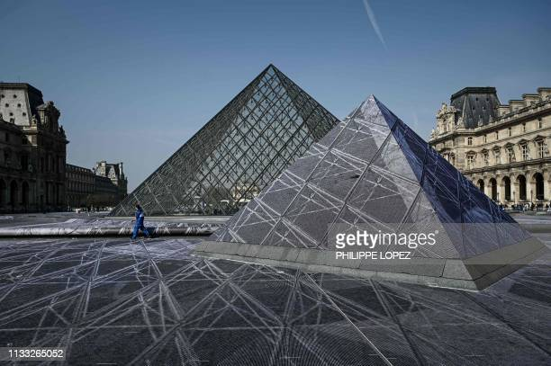 A man walks past small pyramids during preparation works of the installation of French contemporary artist and photographer Jean Rene aka JR in the...