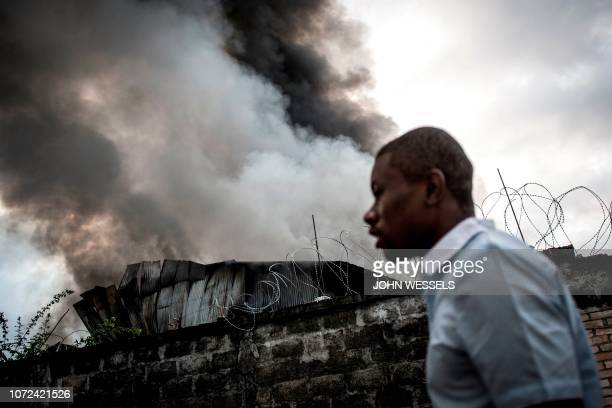 TOPSHOT A man walks past smoke rising from a fire at the independent national electoral commission's warehouse on December 13 2018 in Kinshasa ten...