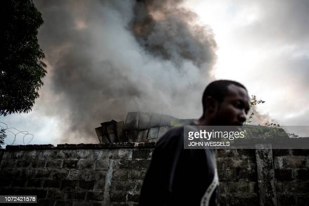 A man walks past smoke rising from a fire at the independent national electoral commission's warehouse on December 13 2018 in Kinshasa ten days ahead...