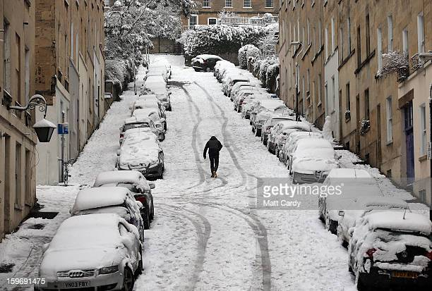 A man walks past snow covered cars parked on Thomas Street on January 18 2013 in Bath England Heavy snow is bringing widespread disruption to many...