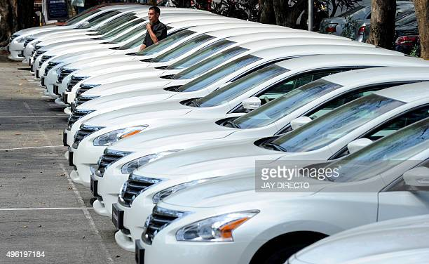 Man walks past some of the hundred of new cars that will be used during the Asia Pacific Economic Cooperation summit to be held in the Philippines...